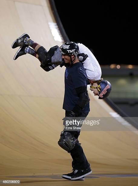 Bob Burnquist of Brazil lifts up Tom Schaar after Schaar won the gold medal in the Skateboard Big Air Finals during the X Games Austin at Circuit of...