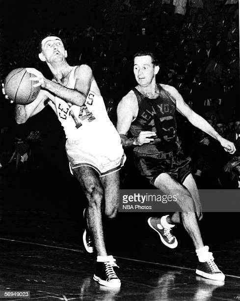 Bob Cousy of the Boston Celtics drives to the basket against Dick McGuire of the New York Knicks at the Boston Garden circa 1950 in Boston...
