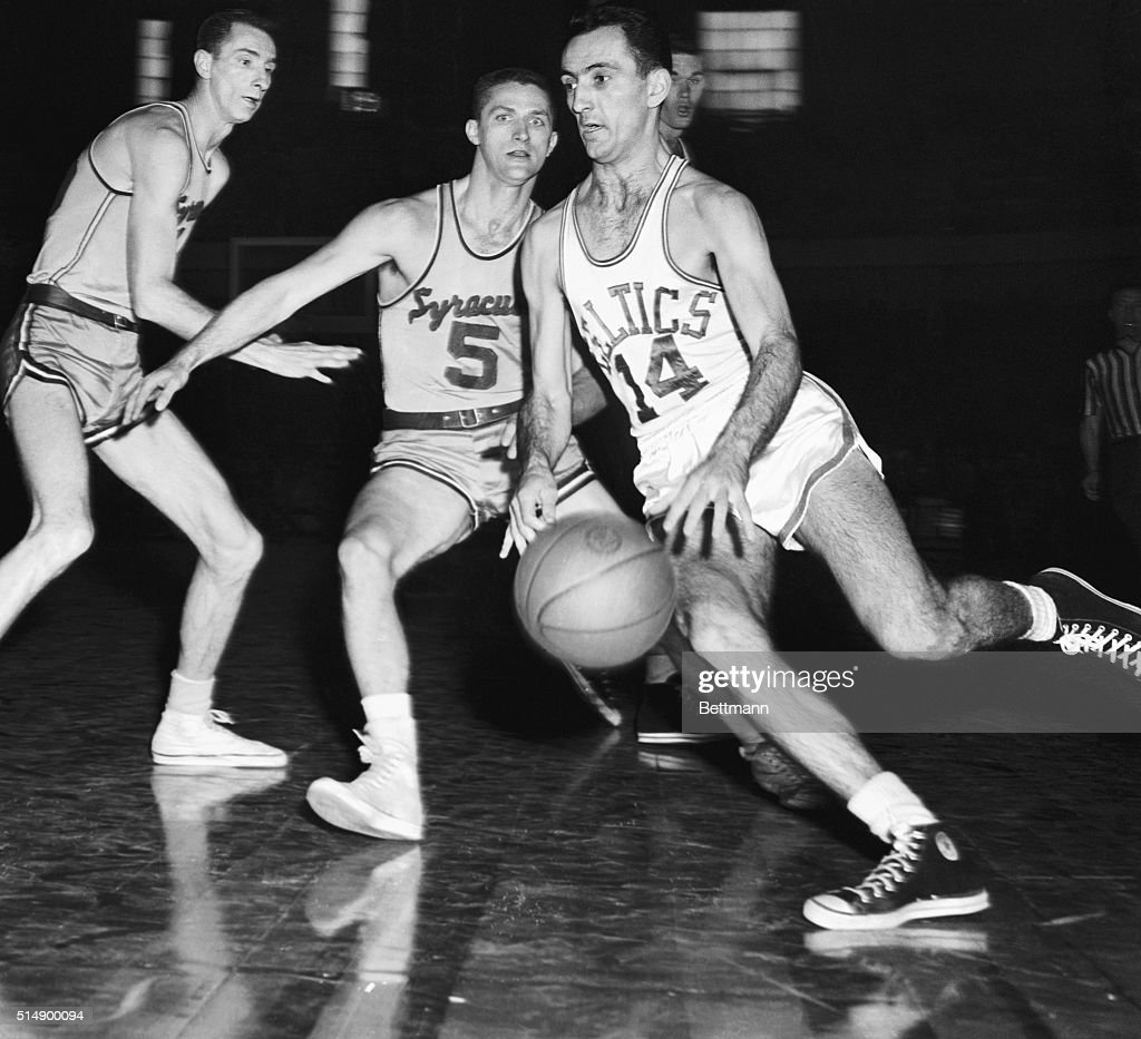 Bob Cousy of the Boston Celtics moves into score through Syracuse Men Red Rocha and Paul Seymour in the second quarter of the playoffs game at the...