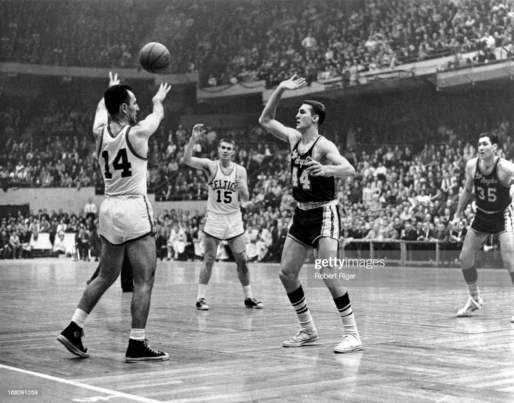 Bob Cousy of the Boston Celtics passes to teammate Tom Heinsohn as Jerry West of the Los Angeles Lakers defends during an NBA game circa 1962 at the...