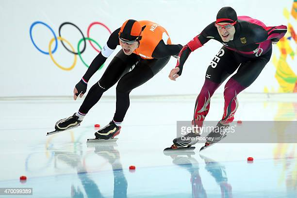 Bob de Jong of the Netherlands and Alexej Baumgaertner of Germany compete during the Men's 10000m Speed Skating event on day eleven of the Sochi 2014...