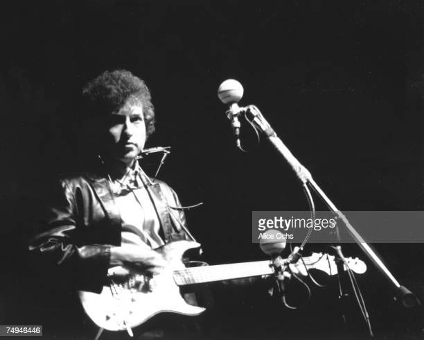 Bob Dylan plays a Fender Stratocaster electric guitar for the first time on stage as he performs at the Newport Folk Festival on July 25 1965 in...