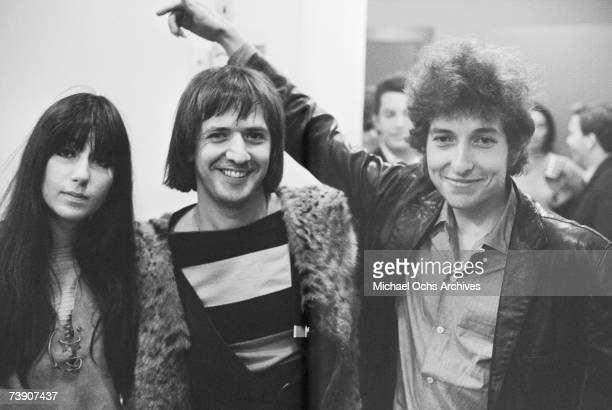 Bob Dylan holds his arm up to embrace pop duo 'Sonny and Cher' as they pose for a portrait at Atlantic Studios in 1965 in New York City New York Cher...