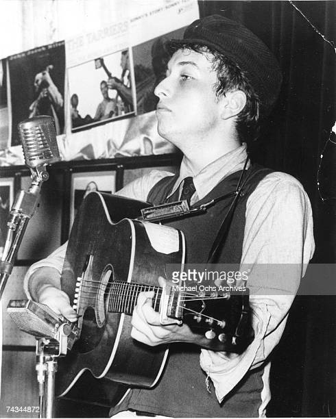Bob Dylan performs on stage at Gerde's Folk City wearing a motorcycle hat with a Gibson acoustic guitar in 1961