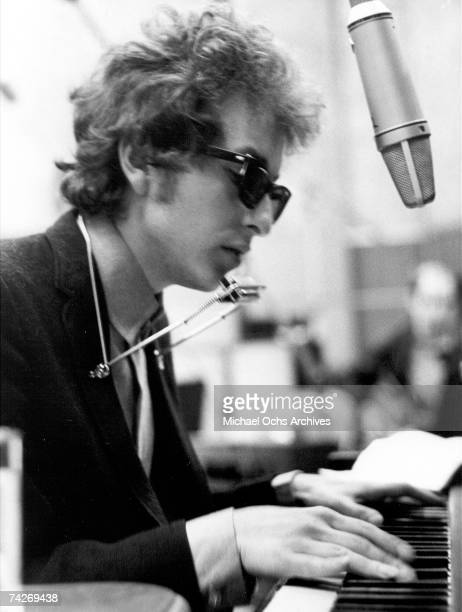 Bob Dylan plays harmonica and piano to a microphone during the recording of the album 'Highway 61 Revisited' in Columbia's Studio A in the summer of...