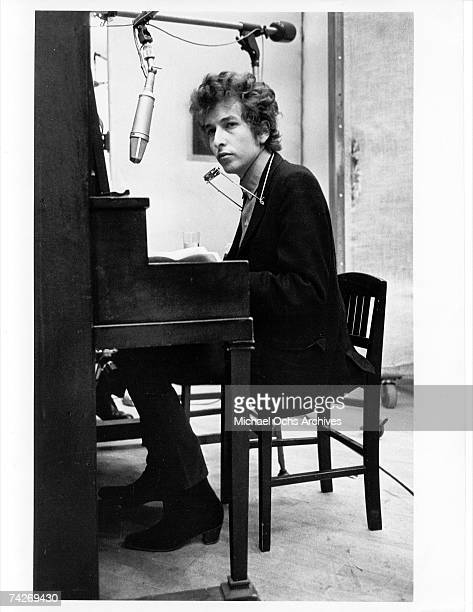Bob Dylan plays piano with a harmonica around his neck while recording his album 'Highway 61 Revisited' on January 1315 1965 in Columbia's Studio A...