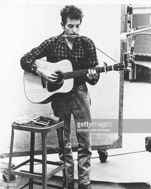 Bob Dylan recording in the studio with his acoustic guitar and an assortment of harmonicas in 1961 or 1962