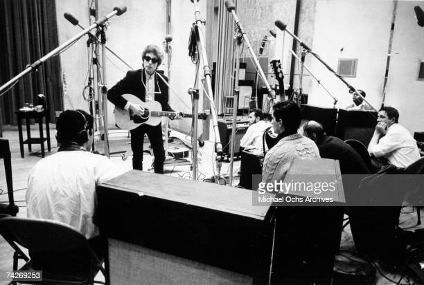 Bob Dylan strums an acoustic guitar with a harmonica around his neck wearing RayBan sunglasses with session guitar player Kenny Rankin seated in the...
