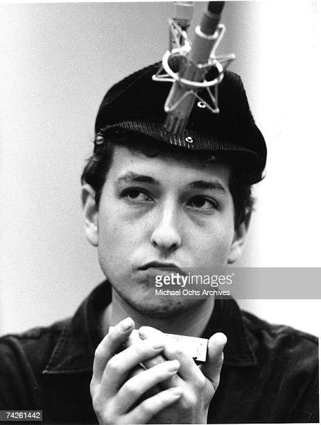 Bob Dylan wearing a motorcycle hat playing harmonica into a microphone in Columbia Recording Studio for a session in September 1961 in New York City...