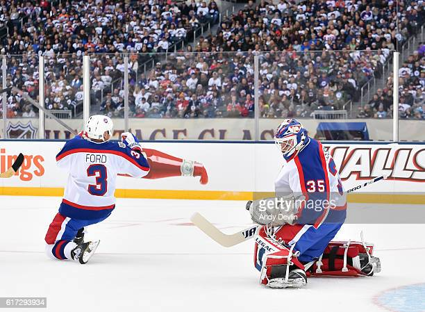 Bob Essensa makes a glove save with Mike Ford of the Winnipeg Jets alumni in front during the 2016 Tim Hortons NHL Heritage Classic alumni game at...