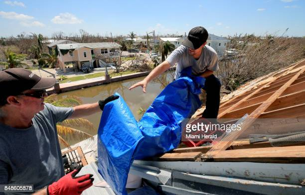 Bob Fiorile and Todd Brown left to right pull a tarp onto the exposed roof of Fiorile's home in Big Pine Key on Sunday Sept 17 2017 Residents were...