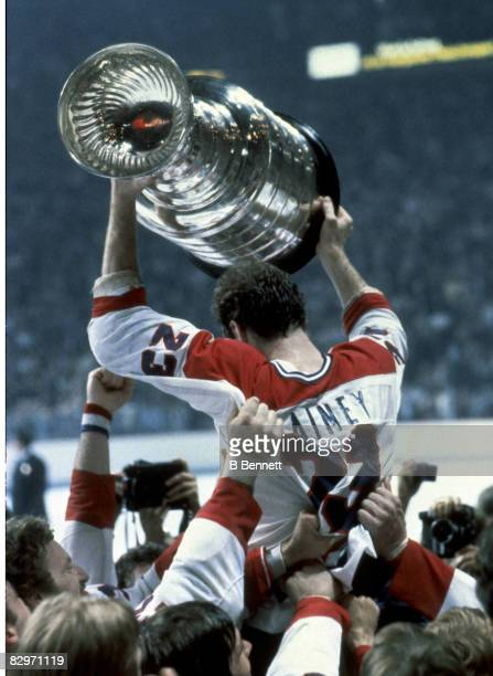 Bob Gainey of the Montreal Canadiens is held aloft by his teammates as he raises the Stanley Cup in victory after his team defeated the New York...