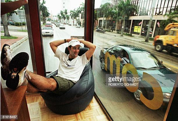 Bob Glassman relaxes on a beanbag chair as he rides a glassenclosed fullyfurnished truck trailer down Biscayne Boulevard in Miami 09 September 1999...