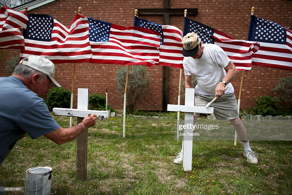 Bob Gordon (L) and Bob Butler paint crosses they placed in front of 16 American flags as they build a memorial in front of Central Christian Disciples of Christ church for the victims of yesterdays shooting at Fort Hood on April 3, 2014 in Killeen, Texas. Iraq war veteran, Ivan Lopez, is reported to be the shooter that claimed three lives and wounded 16 more before taking his own life at Fort Hood.