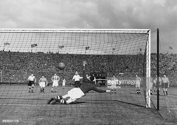 Bob Hesford goalkeeper for Huddersfield Town dives to his right as George Mutch of Preston North End scores the only goal of the match from the...