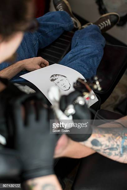 Bob Holmes owner of the Clay Dragon Tattoo shop tattoos a portrait of Republican presidential candidate Donald Trump on the arm of Seth Bailey at his...
