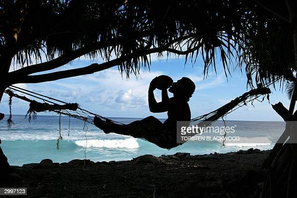 Bob Lisale drinks coconut milk as he watches the king tides pound the coast of Funafuti Atoll 19 February 2004 home to nearly half of Tuvalu's entire...