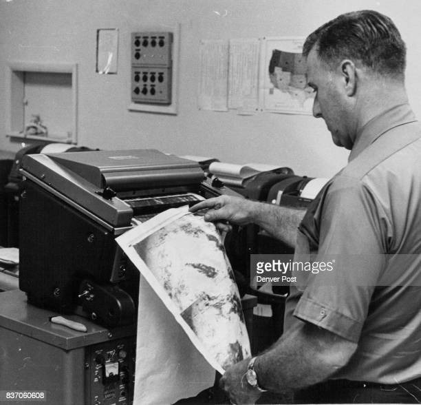 Bob Mangan an aviation forecaster examines one of a dozen satellite photos of the North American continent received daily by the bureau Photos show...
