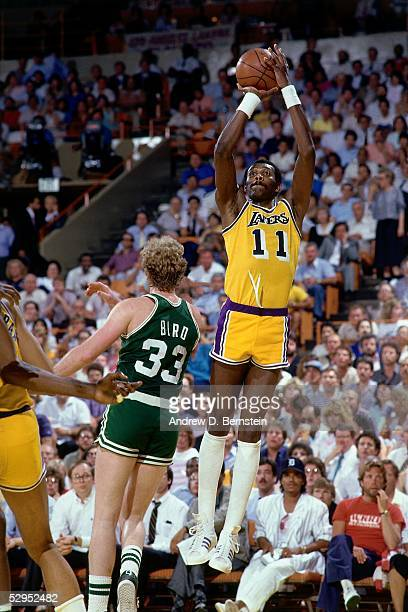 Bob McAdoo of the Los Angeles Lakers shoots a jumpshot against Larry Bird of the Boston Celtics during an NBA game at the Forum circa in Los Angeles...
