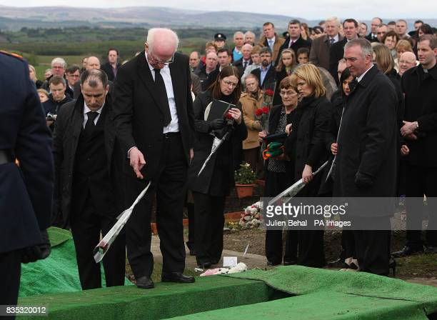 Bob McCallion the father of Robert McCallion throws a single red rose into the grave of his son today The garda was honoured with a State funeral...