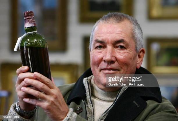 Bob Pert in Gorringes Auctionieers in Lewes East Sussex holding a bottle of whisky he recovered from the wreck of a cargo ship which could fetch more...