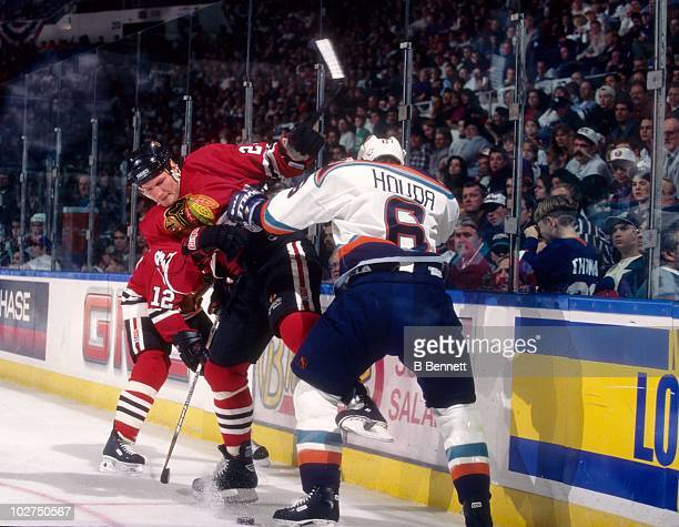 Bob Probert of the Chicago Blackhawks gets checked by Doug Houda of the New York Islanders during an NHL game circa 1997 at the Nassau Coliseum in...