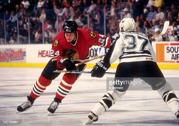 Bob Probert of the Chicago Blackhawks goes for the puck against Brad Lukowich of the Dallas Stars during their game circa September 1997 at the...