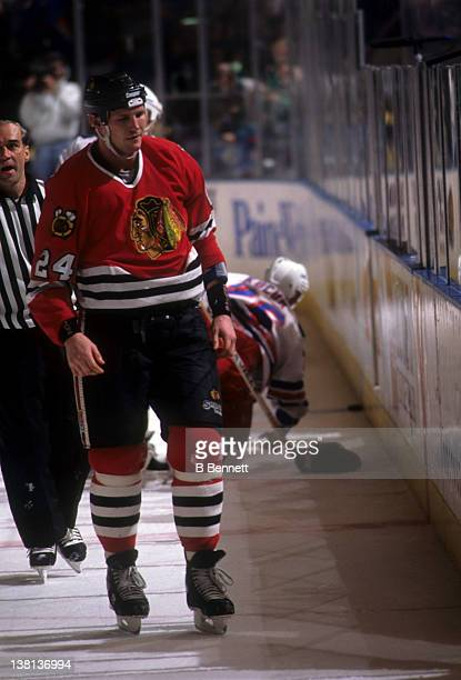 Bob Probert of the Chicago Blackhawks is escorted to the penalty box after his fight with Joe Kocur of the New York Rangers on December 6 1995 at the...