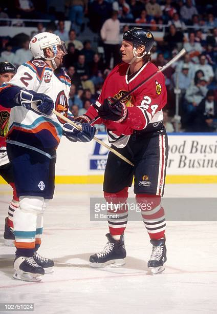 Bob Probert of the Chicago Blackhawks scuffles with Rich Pilon of the New York Islanders during their game on January 25 1997 at the Nassau Coliseum...