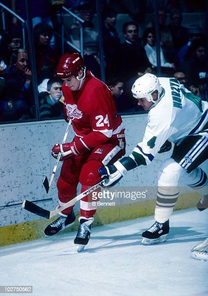 Bob Probert of the Detroit Red Wings battles for the puck with Dana Murzyn of the Hartford Whalers on December 6 1986 at the Hartford Civic Center in...