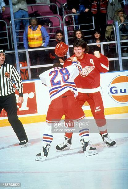 Bob Probert of the Detroit Red Wings fights with Tie Domi of the New York Rangers on December 2 1992 at the Madison Square Garden in New York New York