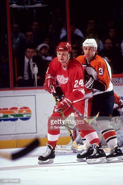 Bob Probert of the Detroit Red Wings sits in front of the goaltender as Garry Galley of the Philadelphia Flyers defends him during an NHL game circa...