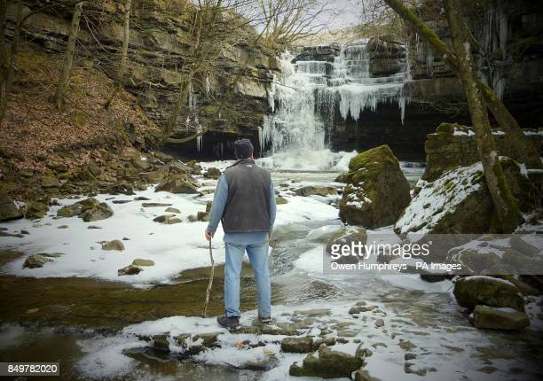 Bob Ripley from Richmond looks at the icicles as The Bow Lee Beck at Gibsons Cave in Teesdale unusally freezes in March after temperatures fell to...