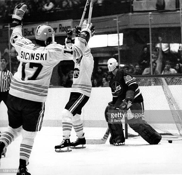 Bob Sicinski and Rosaire Paiement of the Chicago Cougars celebrate after scoring a goal as goalie Ernie Wakely of the Winnipeg Jets looks dejected...