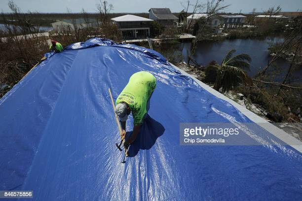 Bob Velasquez puts a giant 40foot by 60foot tarp over the damage done by Hurricane Irma to his home on Big Pine Key September 13 2017 in Big Pine Key...