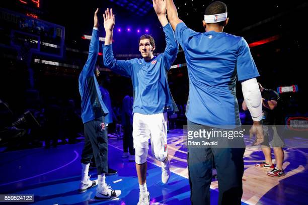 Boban Marjanovic of the Detroit Pistons high fives his teammates before the game against the Indiana Pacers on October 9 2017 at Little Caesars Arena...