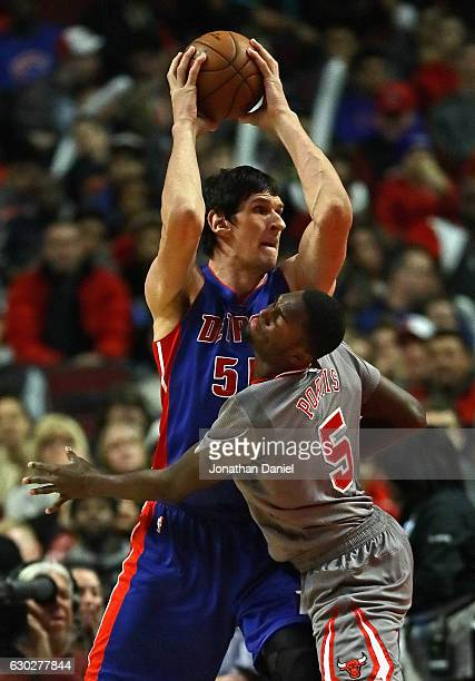 Boban Marjanovic of the Detroit Pistons looks to pass over Bobby Portis of the Chicago Bulls at the United Center on December 19 2016 in Chicago...