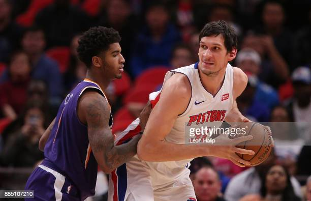 Boban Marjanovic of the Detroit Pistons looks to pass the ball late in the fourth quarter as Marquese Chriss of the Phoenix Suns defends at Little...