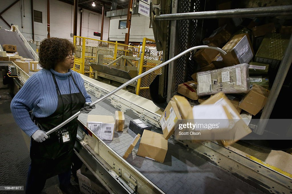 Bobbi Crump loads mail onto a conveyor at the United States Postal Service (USPS) Chicago Logistics and Distribution Center on December 17, 2012 in Elk Grove Village, Illinois. Today is busiest day of the year for the USPS. They expect to move 658 million pieces of mail nationwide, 320 thousand from this facility.