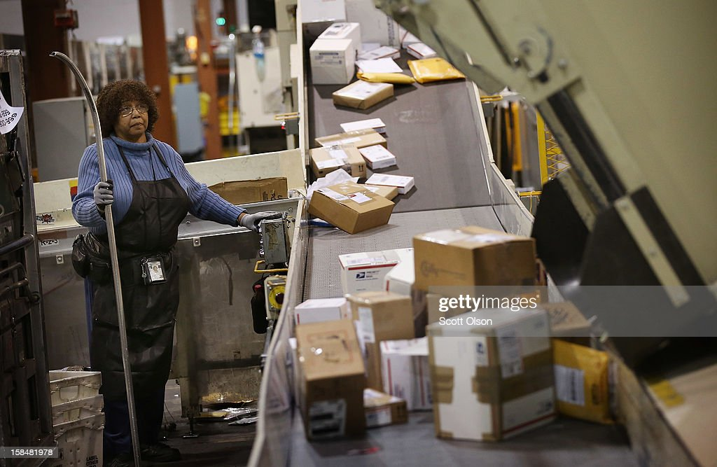 Bobbi Crump moves mail on a conveyor at the United States Postal Service (USPS) Chicago Logistics and Distribution Center on December 17, 2012 in Elk Grove Village, Illinois. Today is busiest day of the year for the USPS. They expect to move 658 million pieces of mail nationwide, 320 thousand from this facility.