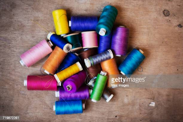 Bobbins of wound thread, silks and cottons in bright colours.