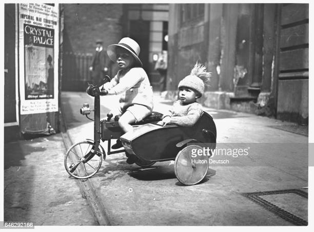 A bobblehatted toddler rides in a tricycle sidecar designed especially for children