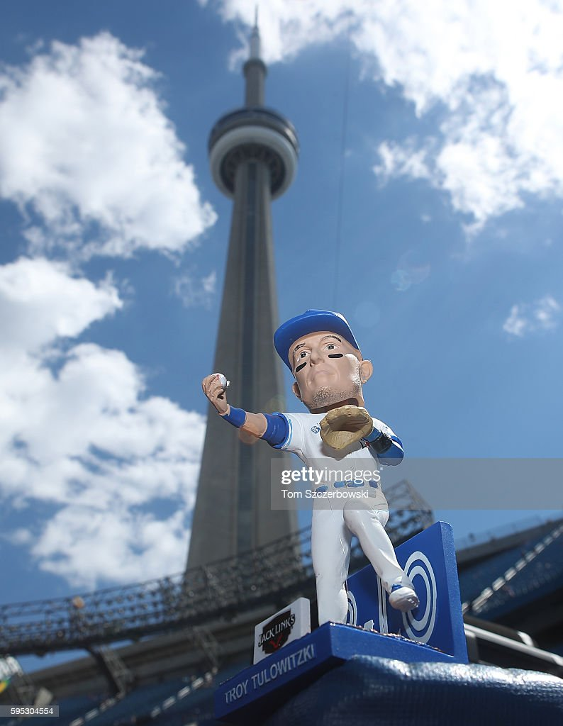 A bobblehead doll of Troy Tulowitzki of the Toronto Blue Jays being handed out to fans on Troy Tulowitzki Bobblehead Day with the CN Tower in the...