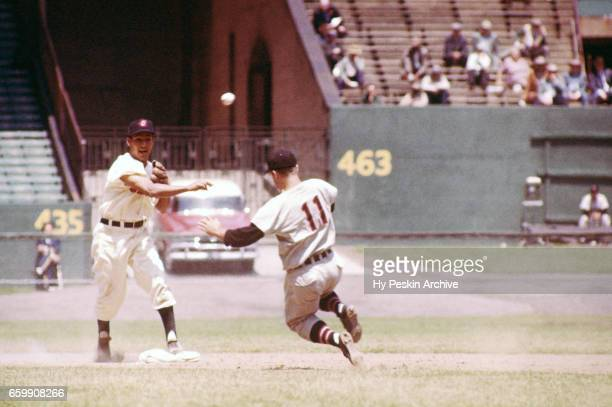 Bobby Avila of the Cleveland Indians steps on the bag and throws to first to complete a double play as Clint Courtney of the Chicago White Sox tries...