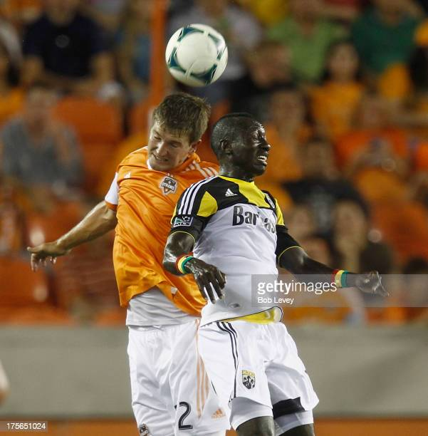 Bobby Boswell of Houston Dynamo and Dominic Oduro of Columbus Crew vie for a header at BBVA Compass Stadium on August 3 2013 in Houston Texas
