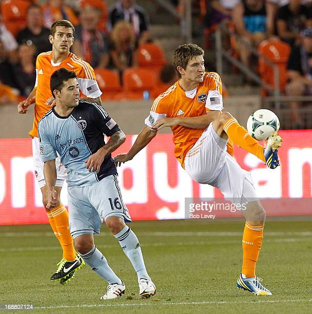Bobby Boswell of Houston Dynamo gains control of the ball as Claudio Bieler of Sporting KC applies some pressure at BBVA Compass Stadium on May 12...