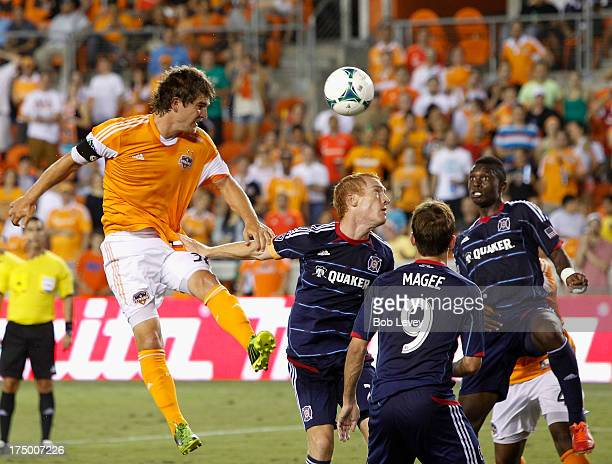 Bobby Boswell of Houston Dynamo heads the ball on goal as Mike Magee of Chicago Fire and at BBVA Compass Stadium on July 27 2013 in Houston Texas