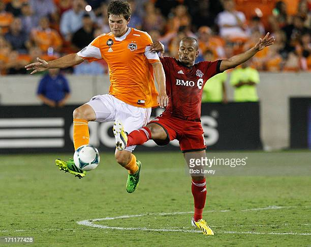 Bobby Boswell of Houston Dynamo keeps the ball away from Robert Earnshaw of Toronto FC at BBVA Compass Stadium on June 22 2013 in Houston Texas