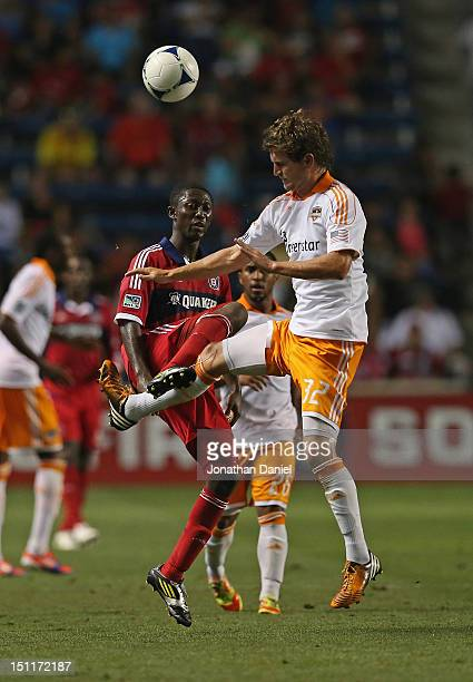 Bobby Boswell of the Houston Dynamo moves in to kick the ball away from Patrick Nyarko of the Chicago Fire during an MLS match at Toyota Park on...