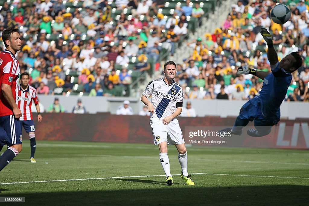 Bobby Burling #2 and Eric Avila #15 of Chivas USA and <a gi-track='captionPersonalityLinkClicked' href=/galleries/search?phrase=Robbie+Keane&family=editorial&specificpeople=171824 ng-click='$event.stopPropagation()'>Robbie Keane</a> #7 of the Los Angeles Galaxy watch as goalkeeper Dan Kennedy #1 of Chivas USA dives to try for the save on a shot by Jack McBean #32 of the Los Angeles Galaxy (not in photo) which resulted in a goal during the second half of their MLS match at The Home Depot Center on March 17, 2013 in Carson, California. Chivas USA and the Los Angeles Galaxy played to a 1-1 draw.